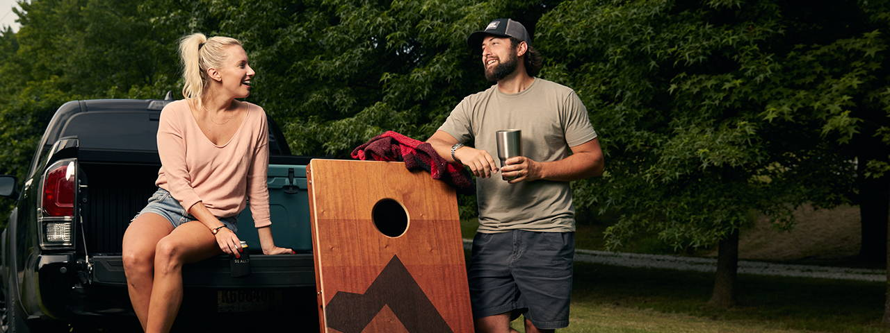 Two Friends Tailgating Outdoors with Cornhole Board