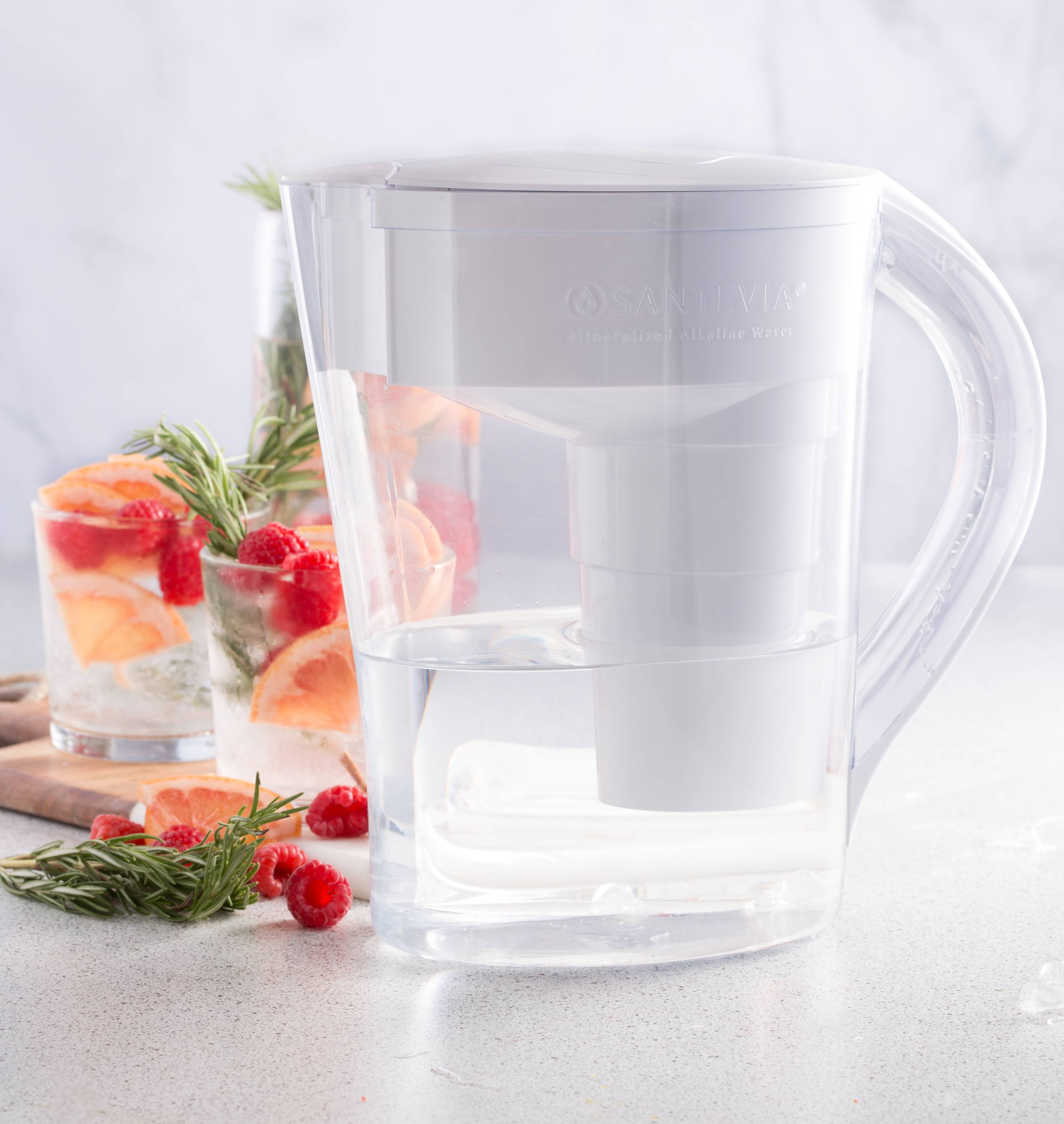 Santevia MINA Pitcher with glasses of alkaline water infused with grapefruit, raspberries, and rosemary.