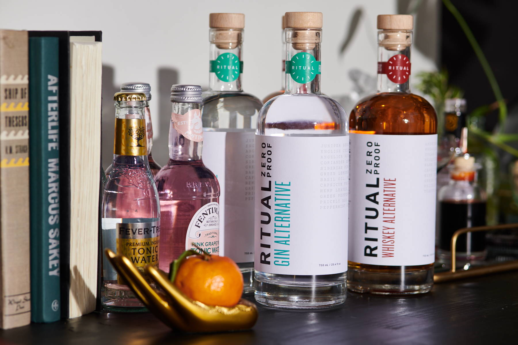 Bottles of Ritual spirit-free gin and whiskey alternatives, arranged with cocktail mixers and bar accessories.