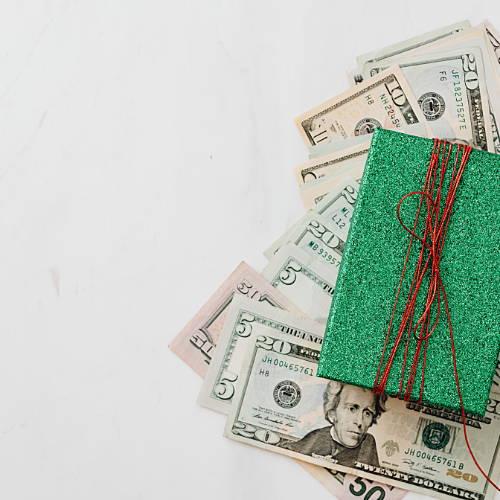 $20 bills under a green Christmas present