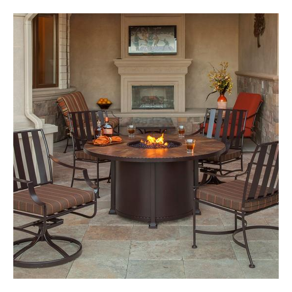 A steel fire pit surrounded by dining chairs
