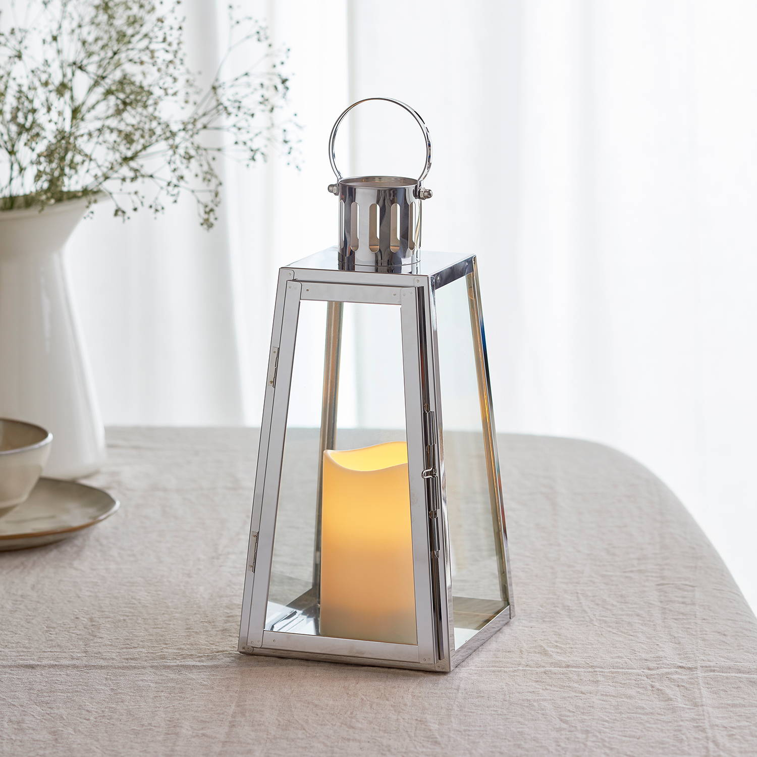 Stainless steel battery lantern with LED candle inside illuminated and sat on table covered with white tablecloth
