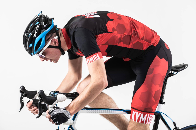 A man dressed in KYMIRA sportswear cycling on his Road Bike