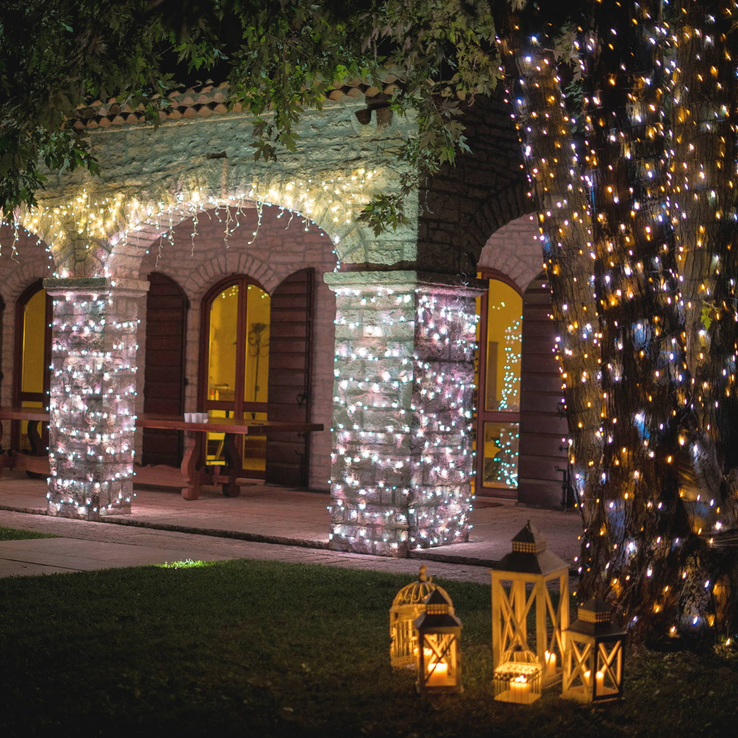 Gold edition Twinkly string lighting displayed outside home with illuminated outdoor lanterns