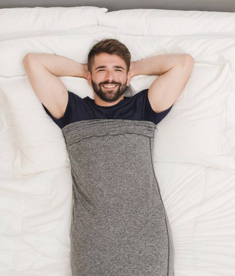 man in sleep pod laying in bed