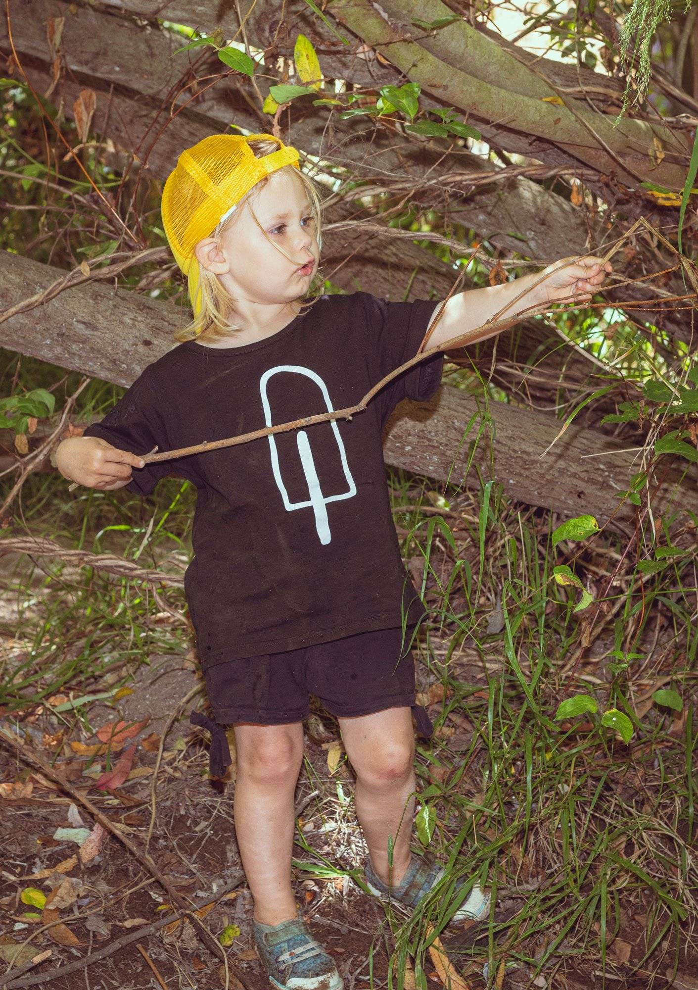 Young boy with a yellow cap and black shirt with popsicle design