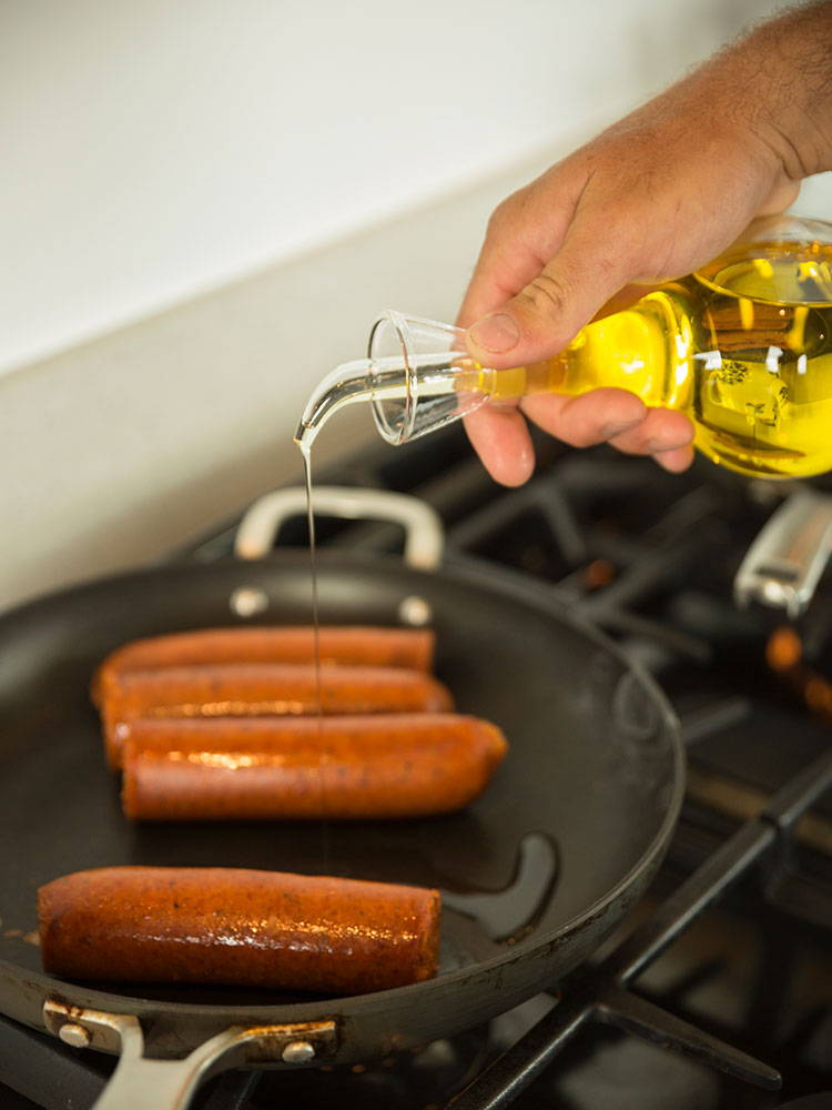 pouring oil over sausages
