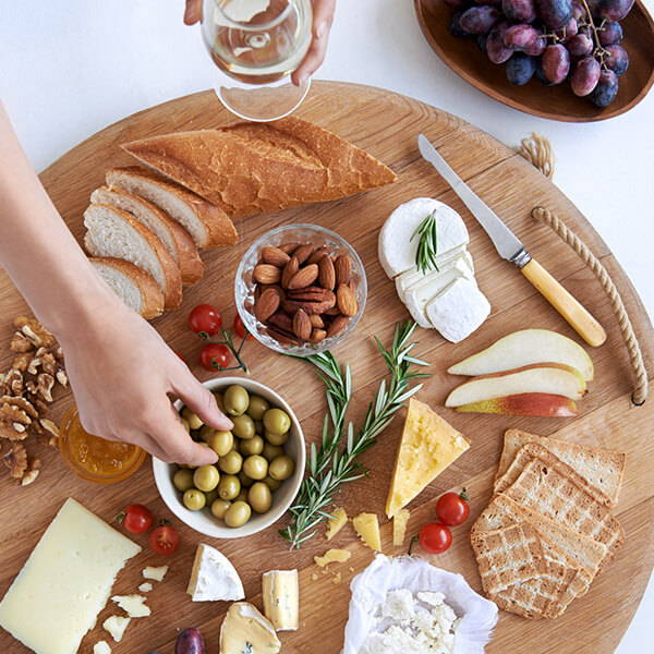 High Quality Organics Express Cheese board with olives and bread and almonds