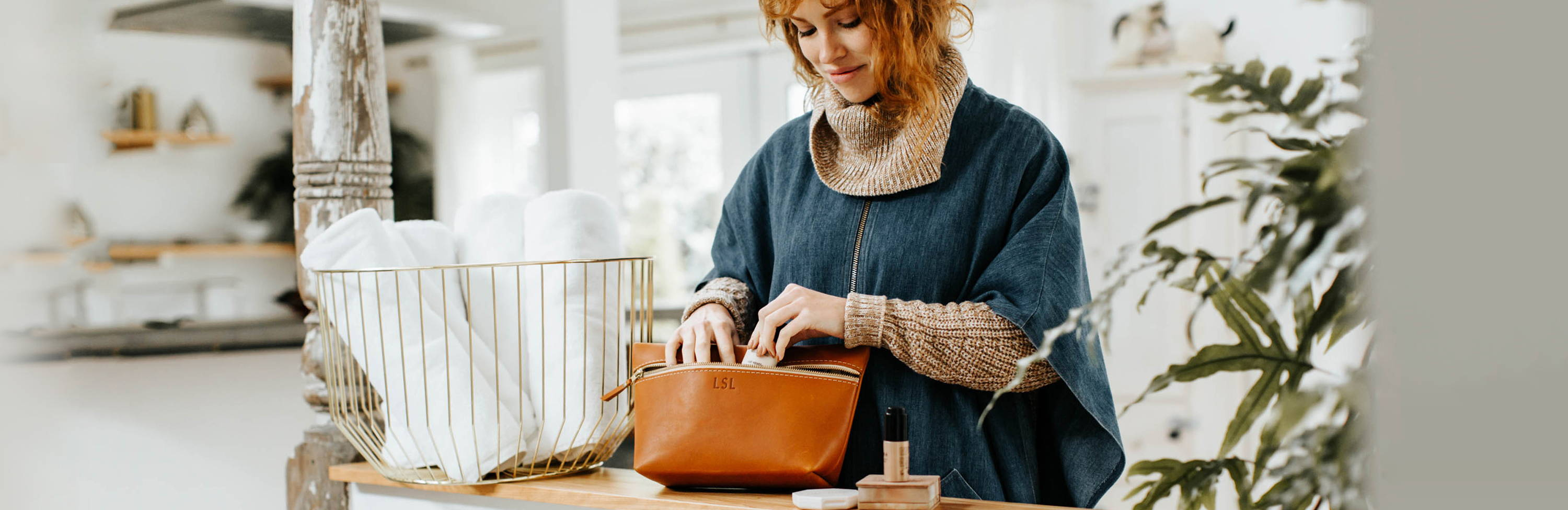 a smiling woman putting makeup and cosmetics into her handmade leather makeup bag by portland leather goods