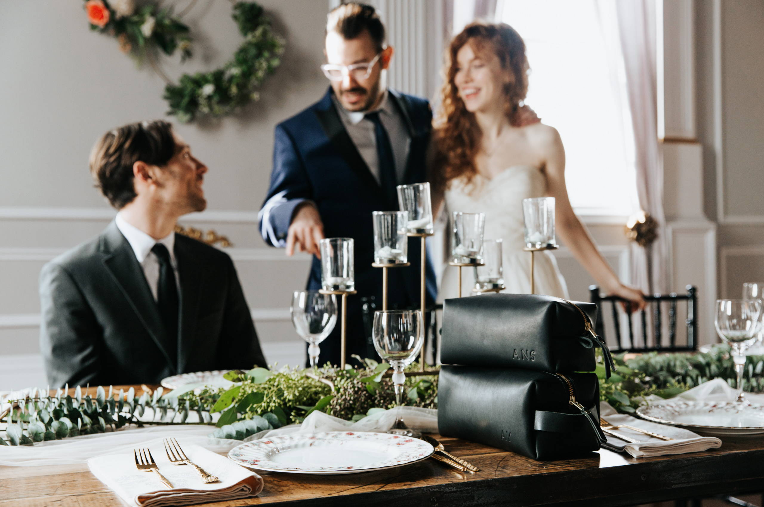 groomsman talking to and laughing with bride and groom at a table adorned with black leather dopp kits