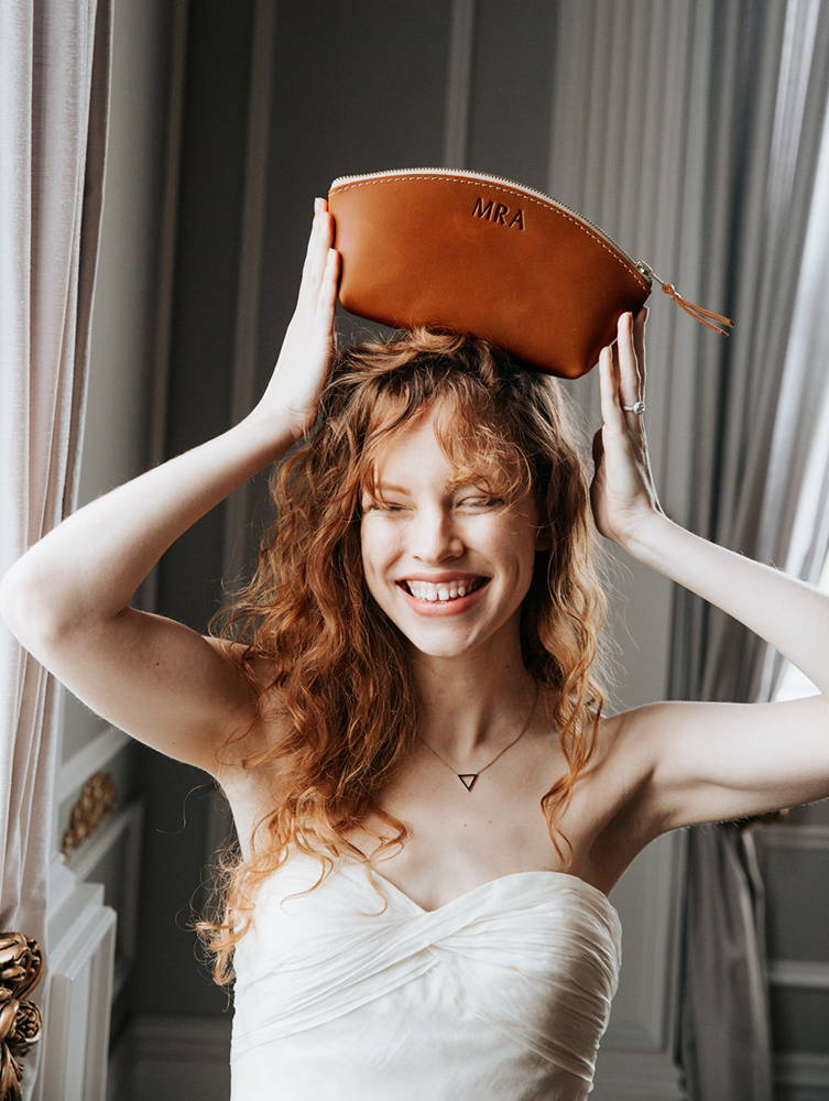 Bride smiling with personalized leather makeup bag on her head