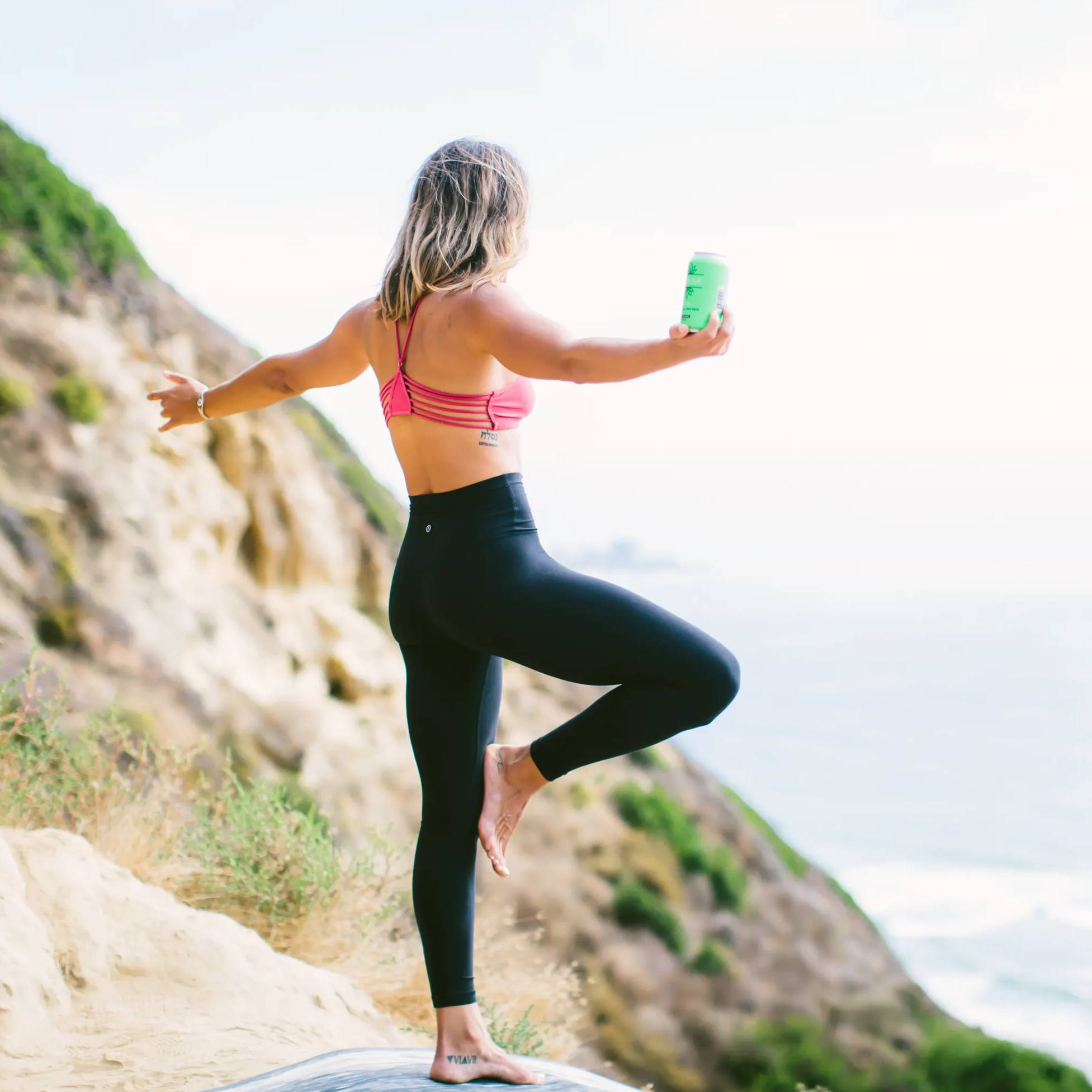 Woman stands over an ocean overlook, standing in a yoga pose and holding a can of Grüvi IPA