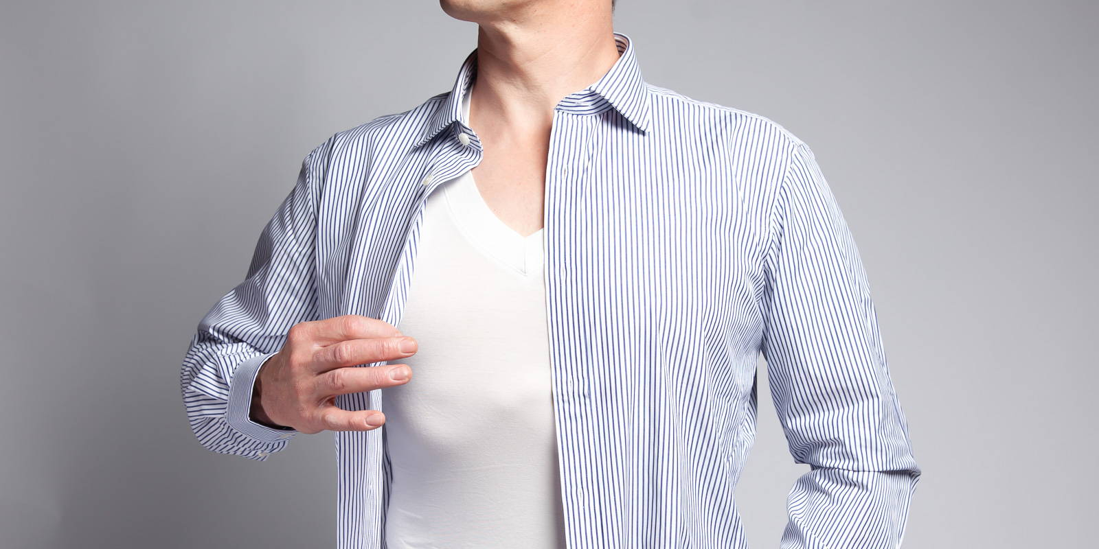 A picture of a white v neck bamboo undershirt under an open blue and white dress shirt