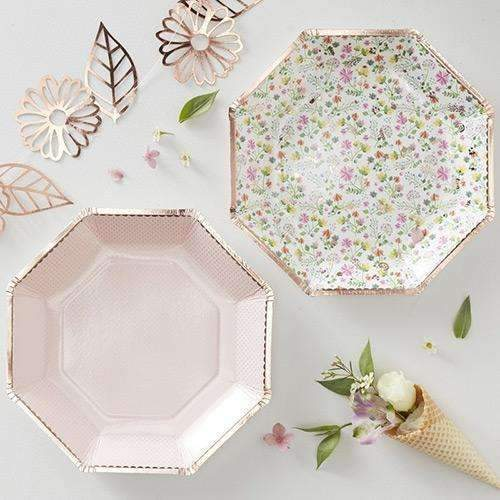 A top-down photo of a table set up with the Ditsy Floral baby shower range with a pink paper party plate and a floral patterned plastic plate, plus rose gold leaf and flower confetti and a flower cone