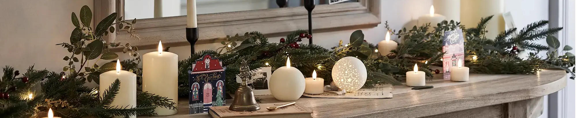 Side table in hallway decorated with assortment of candles and festive garland