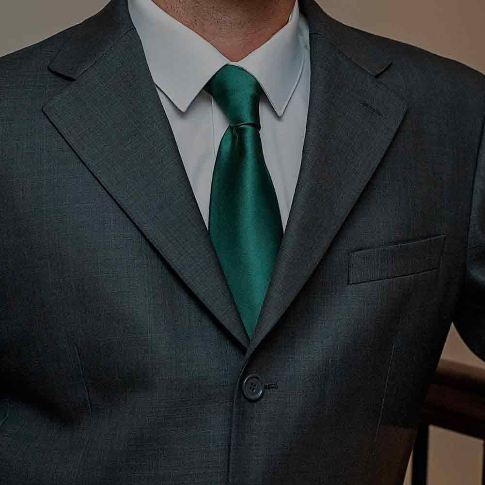 Man wearing a hunter green necktie and gray suit