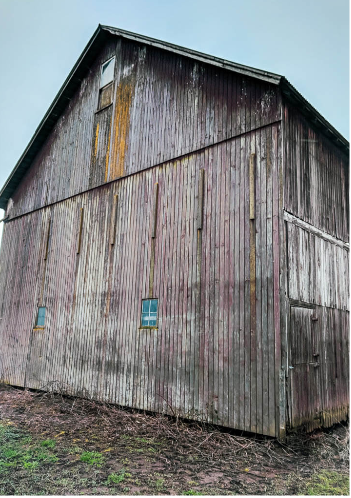 Old barn with weathered patina wood and small glass windows.
