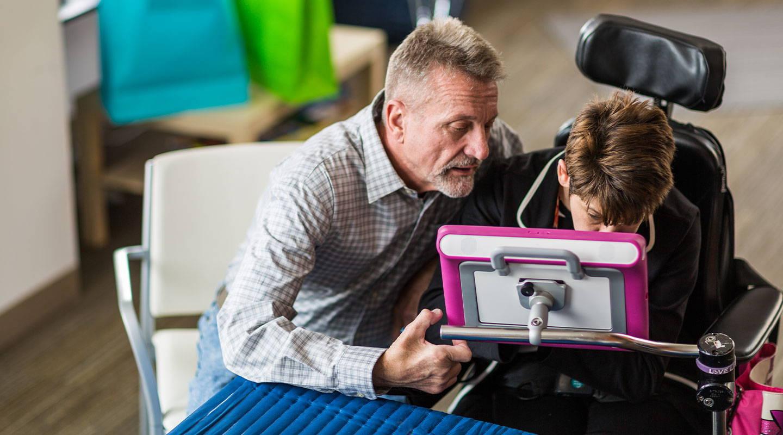 Elternteil kommuniziert dank eines Gerätes von Tobii Dynavox erfolgreich mit seinem Kind