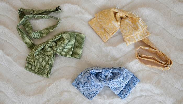 Three womens floppy bow ties laying on a fur blanket
