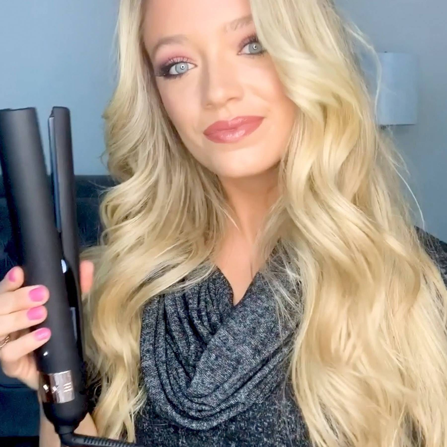 blonde woman curling hair with tyme iron pro obsidian