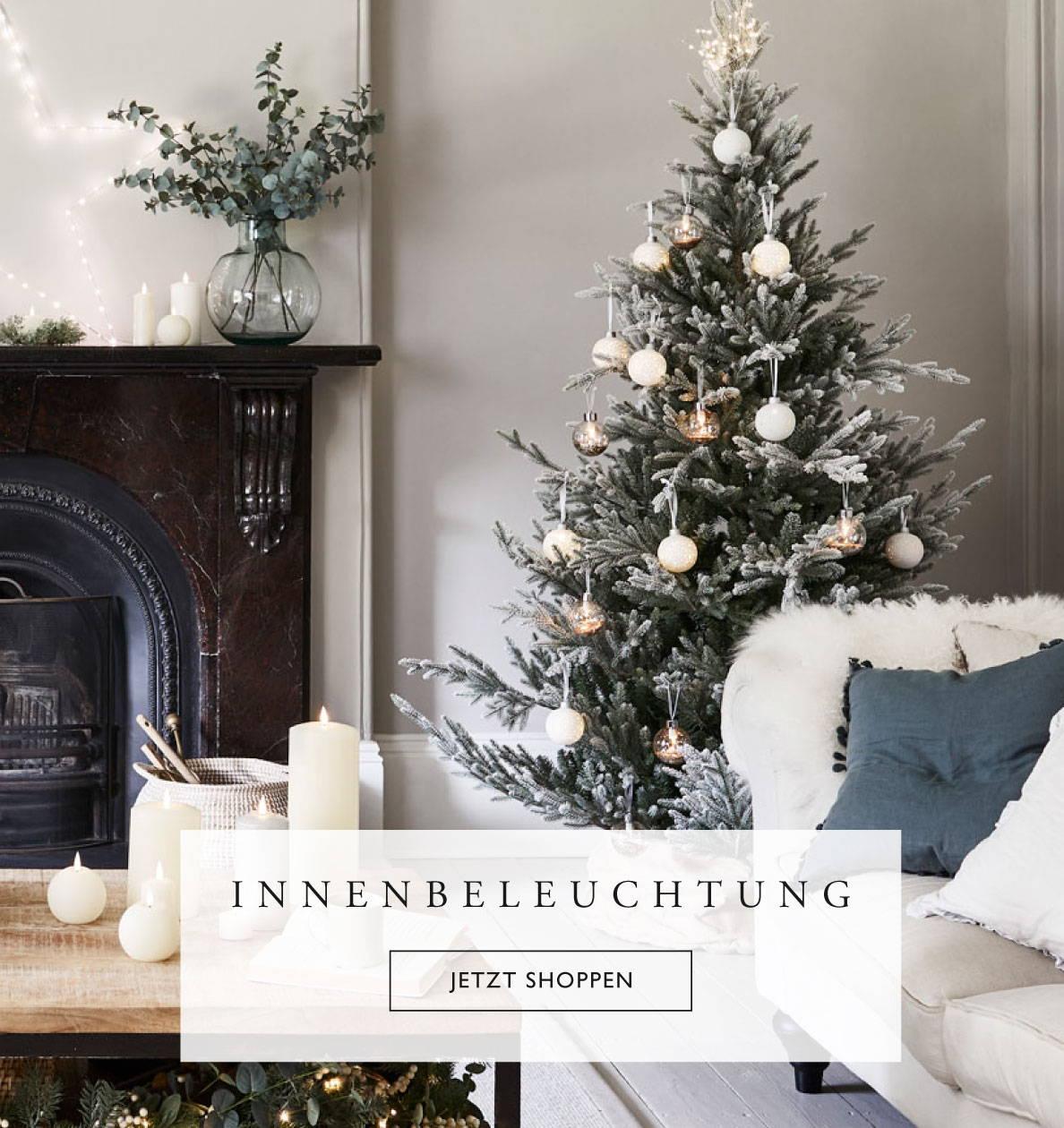 Wohnzimmer mit geschmücktem Weihnachtsbaum, Kamin, Sofa und Kerzen