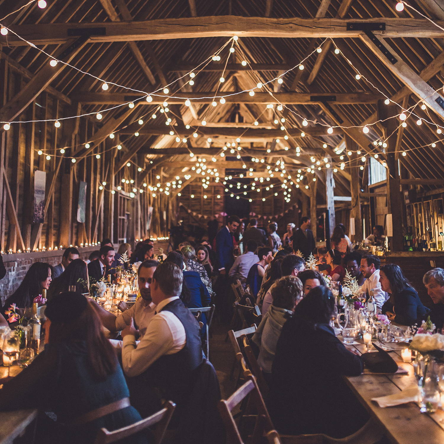 A barn filled with wedding guests and dressed with white cable festoon lights