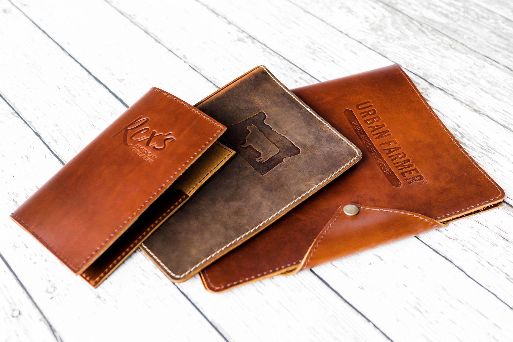3 sizes of custom firebranded leather menu covers and checkbooks