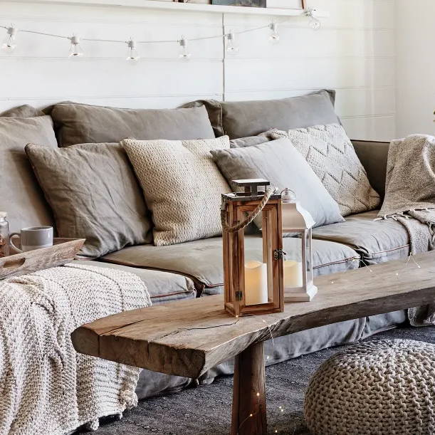 Cosy living room space with an indoor lantern, LED lights and textured sofa accessories