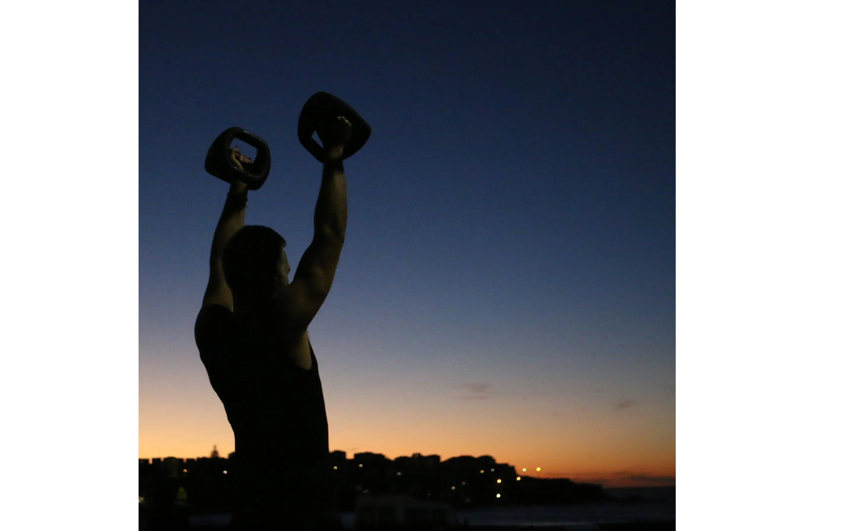 A female athlete training with YBells at dawn on Bondi Beach.