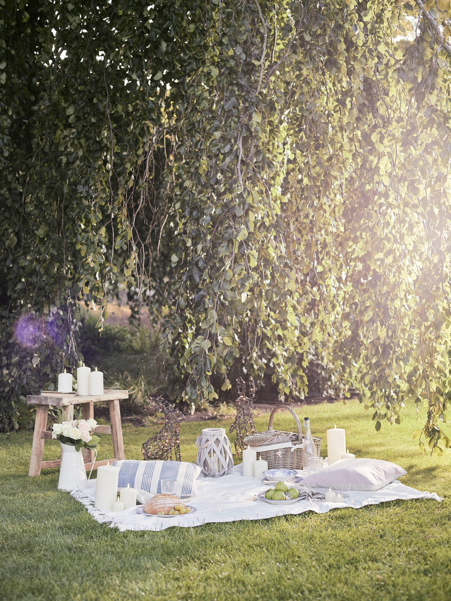 Spring picnic setting in garden with outdoor candles and lanterns