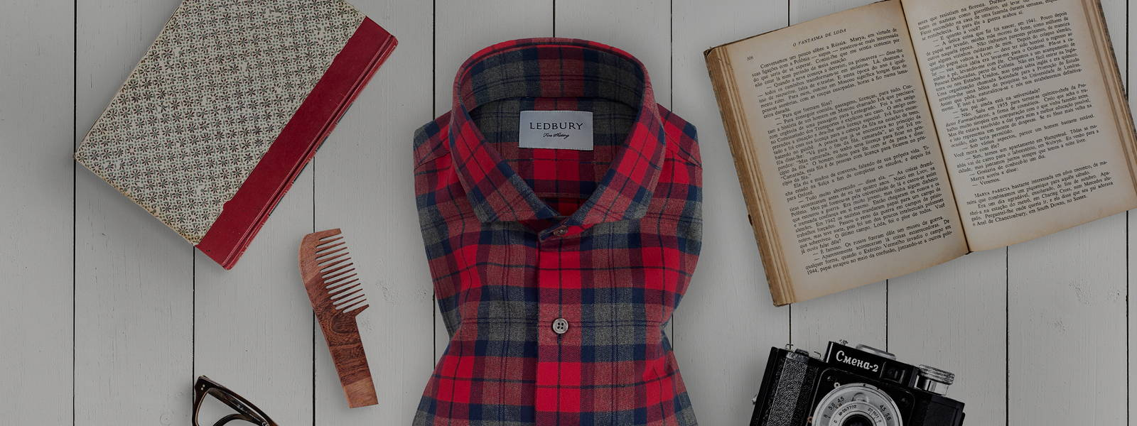 The Red Burrell Flannel on a white wooden background with vintage books, camera, comb, and glasses.