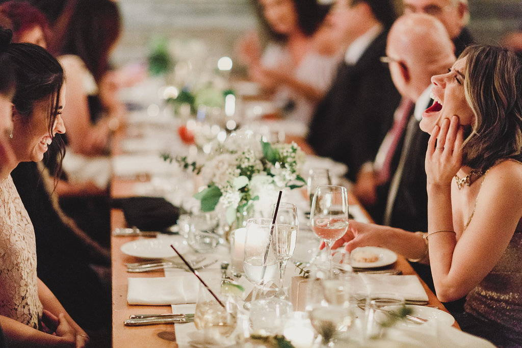 Wedding guests having a laugh among centrepieces by wedding florist May Flowers