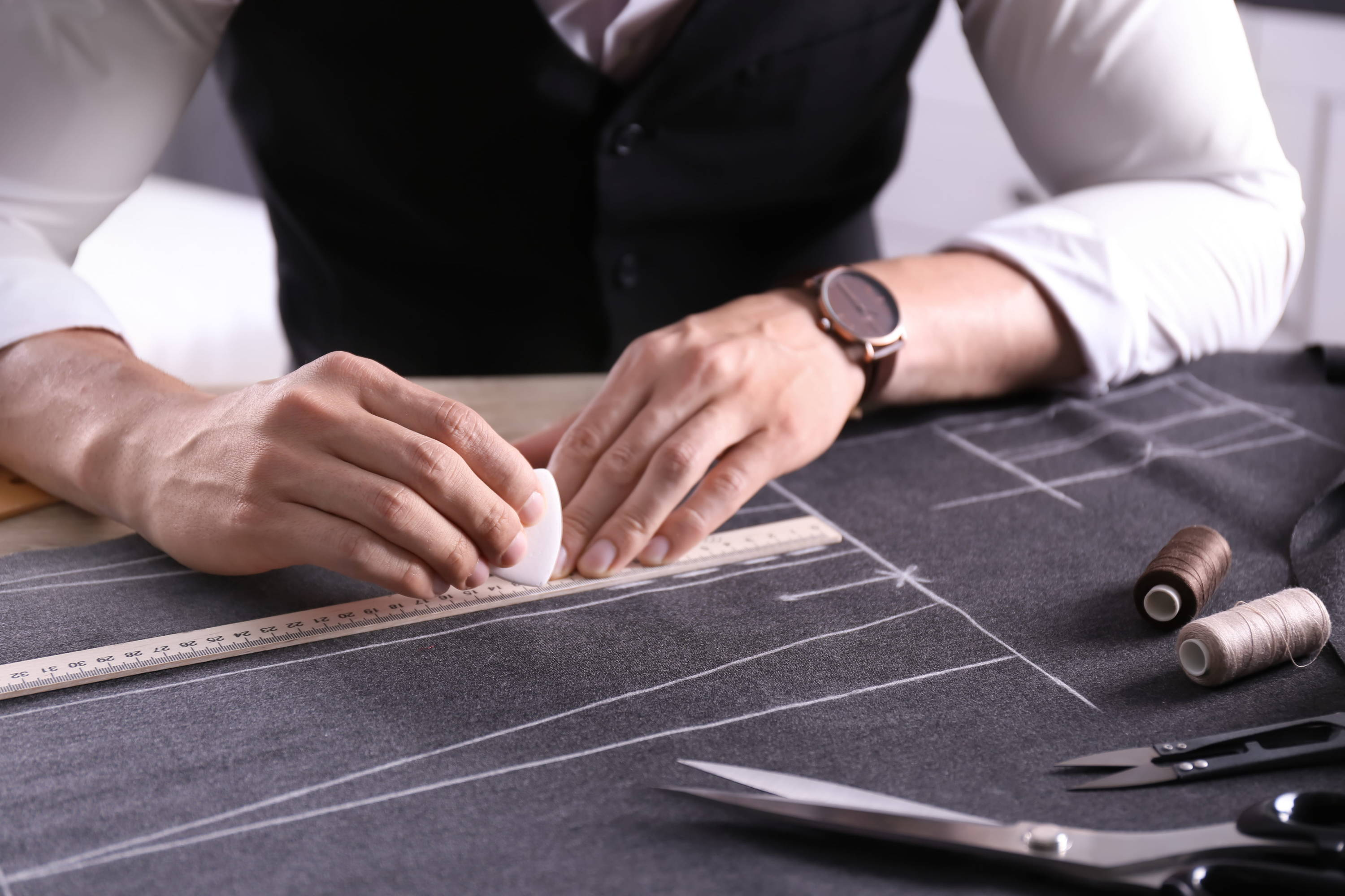 Bespoke tailor carefully chalks out the pattern for a bespoke suit before cutting the suiting fabric