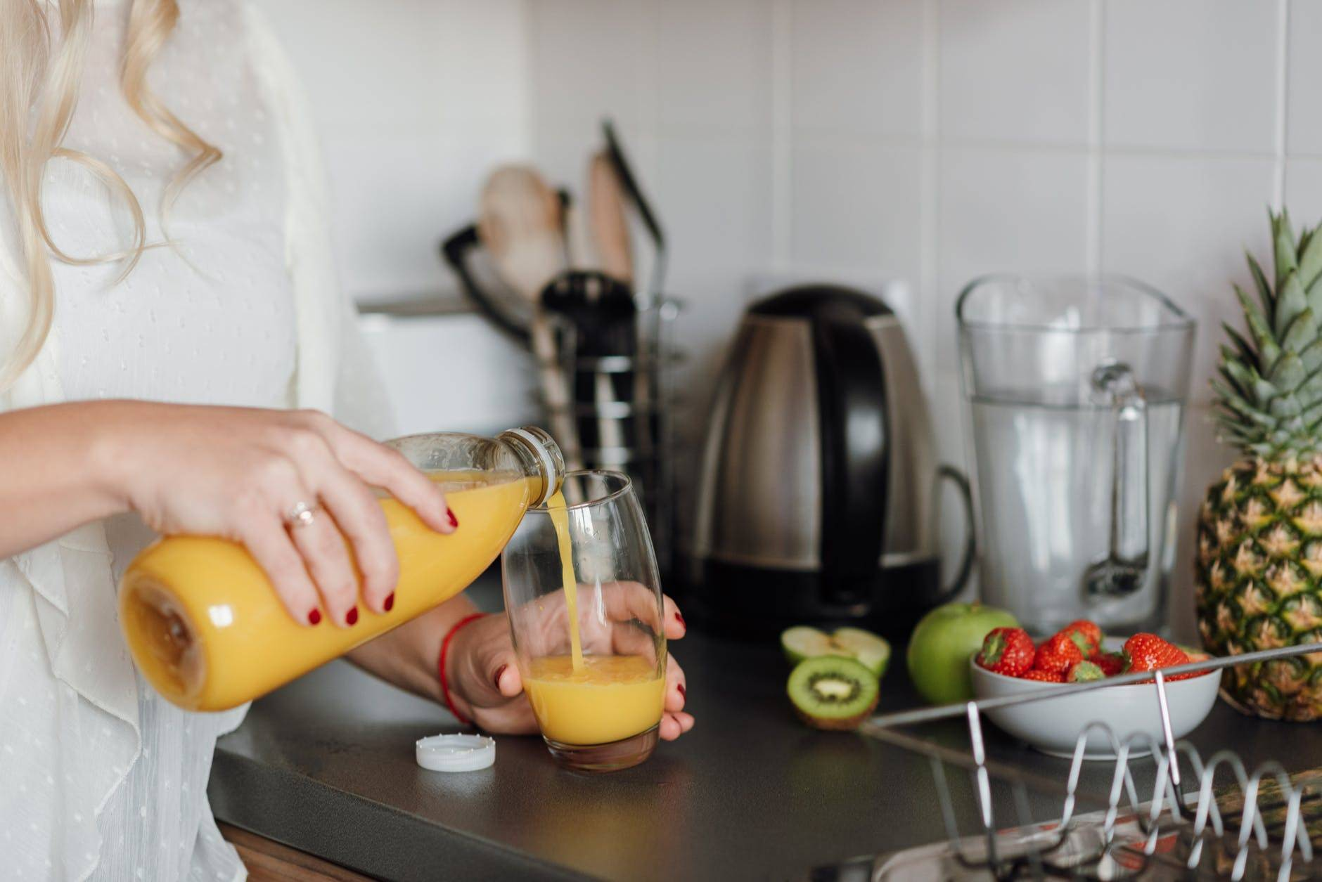 Woman Pouring Juice Standing Near Table With Fruits