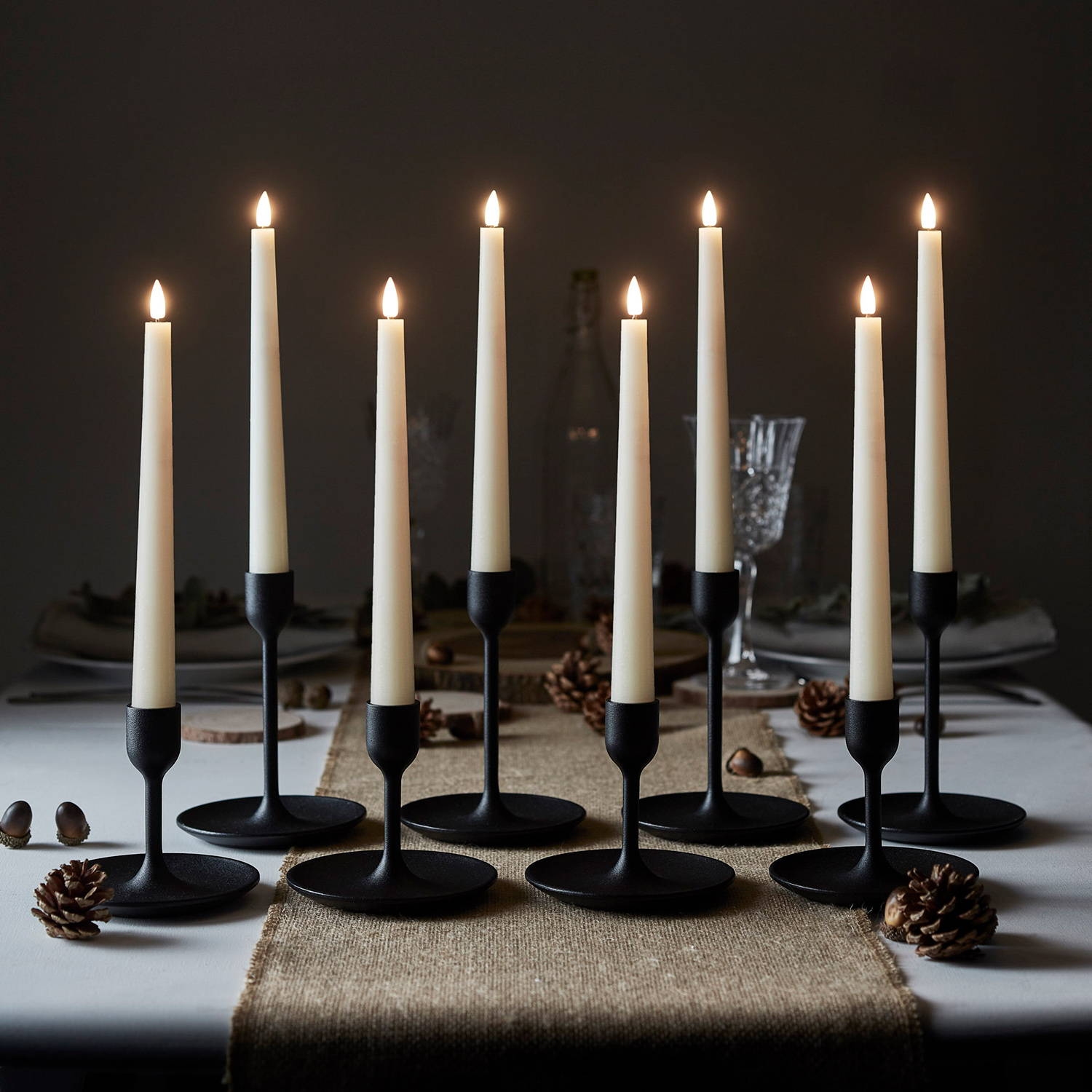 Taper candles illuminated on fall table