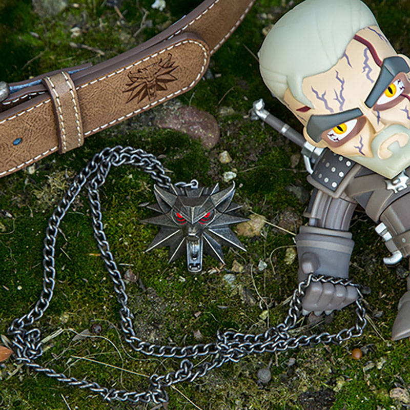 Photo of several Witcher products, including a belt, toy and necklace