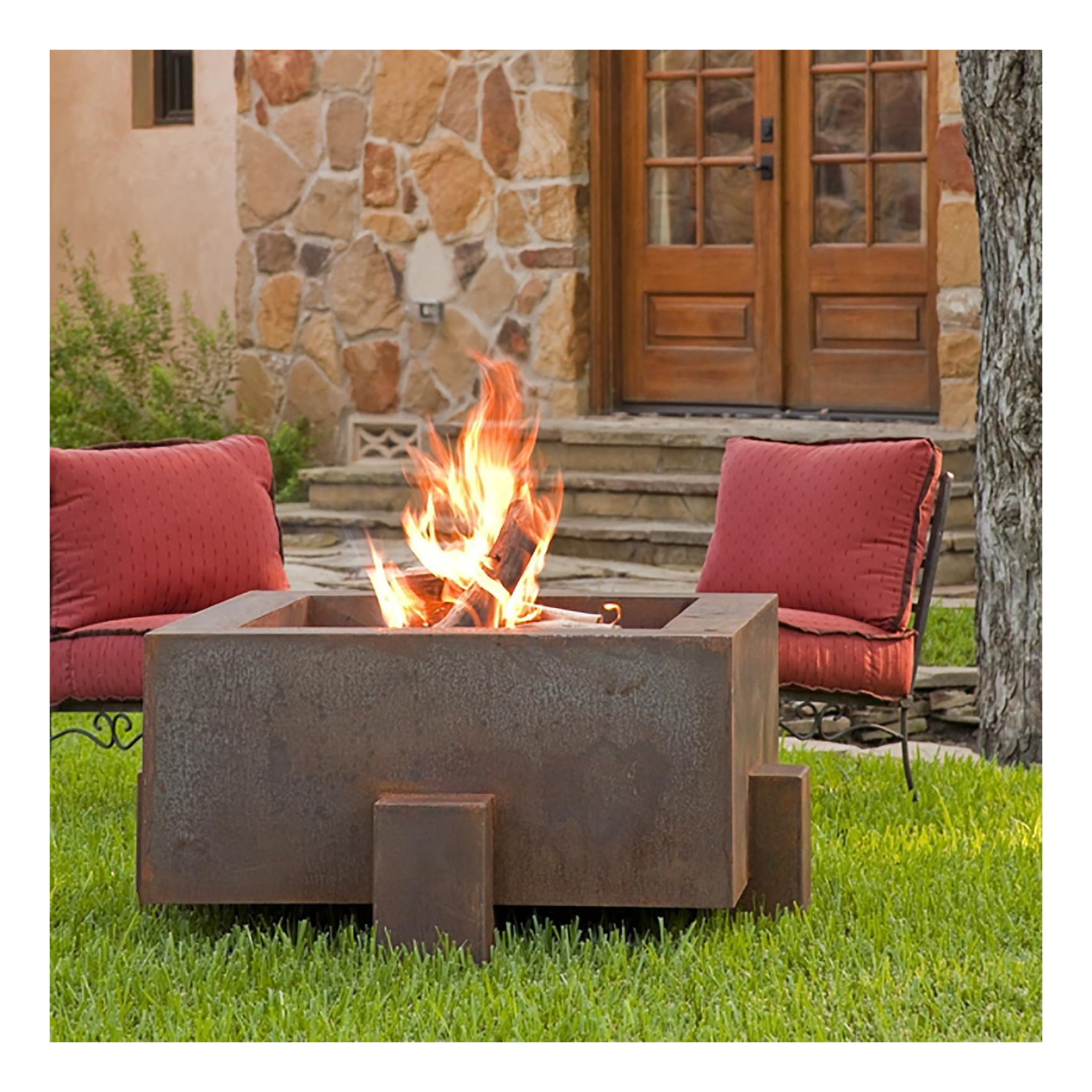 A cor-ten fire pit setup in the grass of a backyard