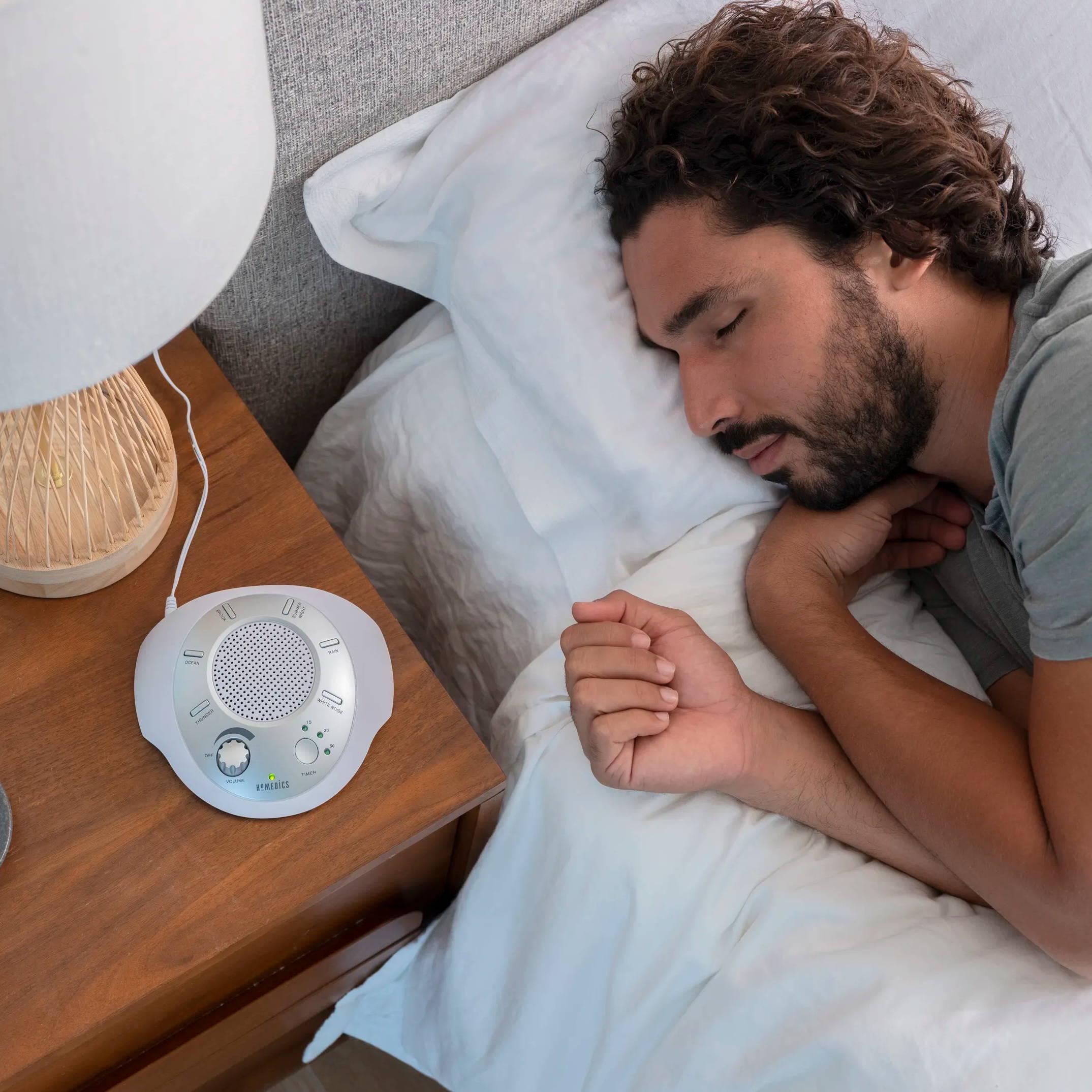 Man sleeping next to sound machine