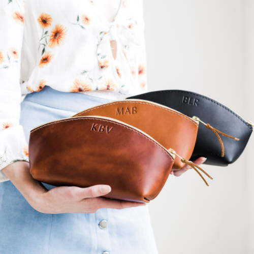 woman holding three colors of portland leather goods handmade make up bags