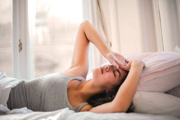 Woman In Grey Tank Top Lying I Bed With Hand On Head