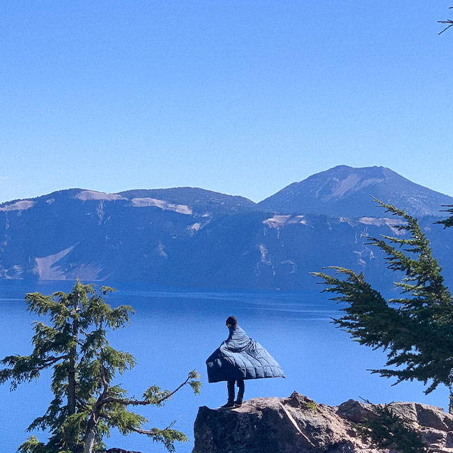 Man hiking with a view of Crater Lake in a Rumpl blanket