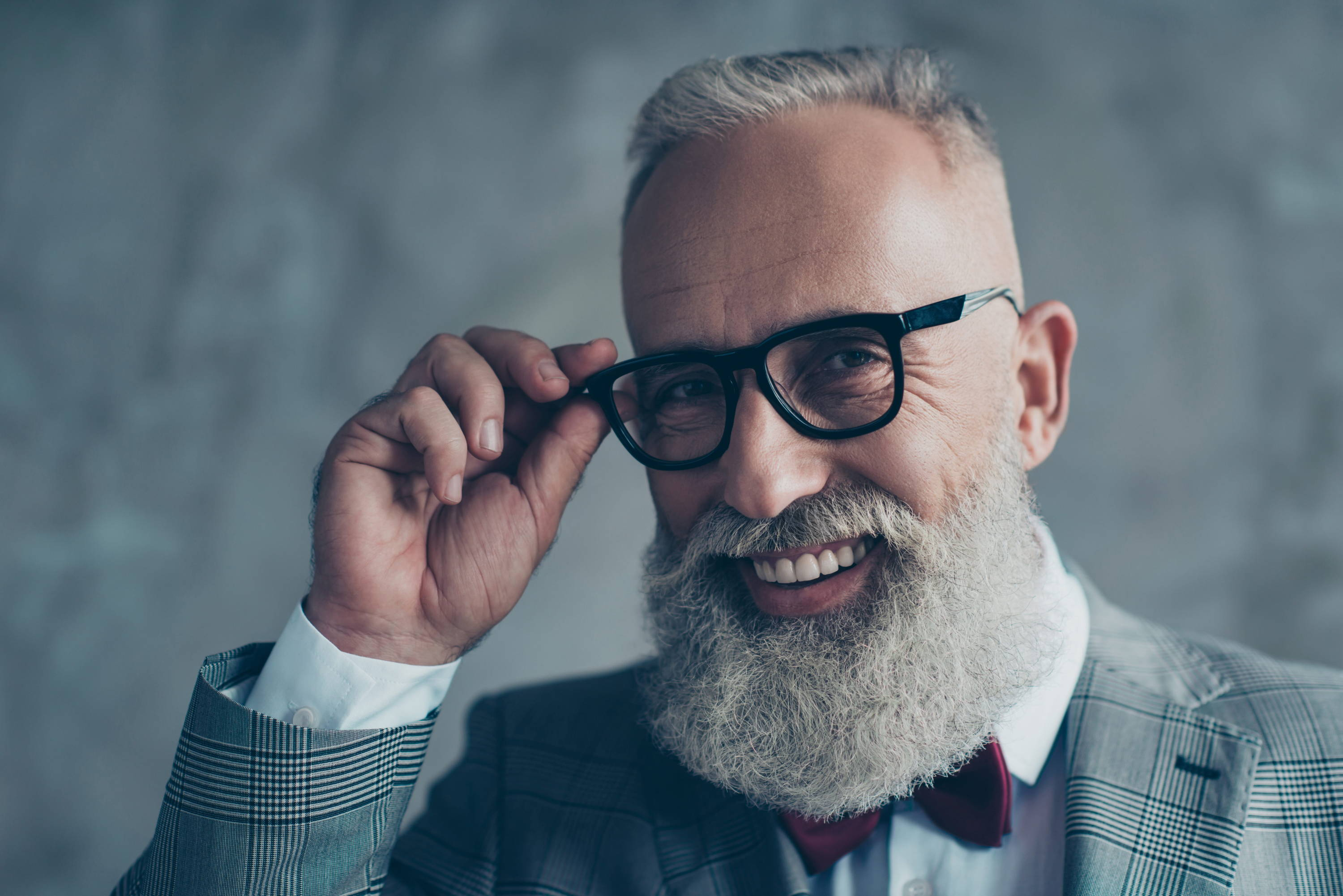 Chic silver haired man with bow tie and glasses embodies hipster style