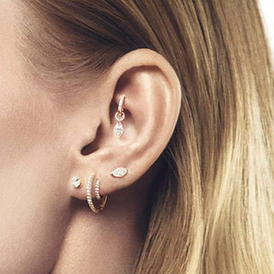 Ear with multiple earrings stacked