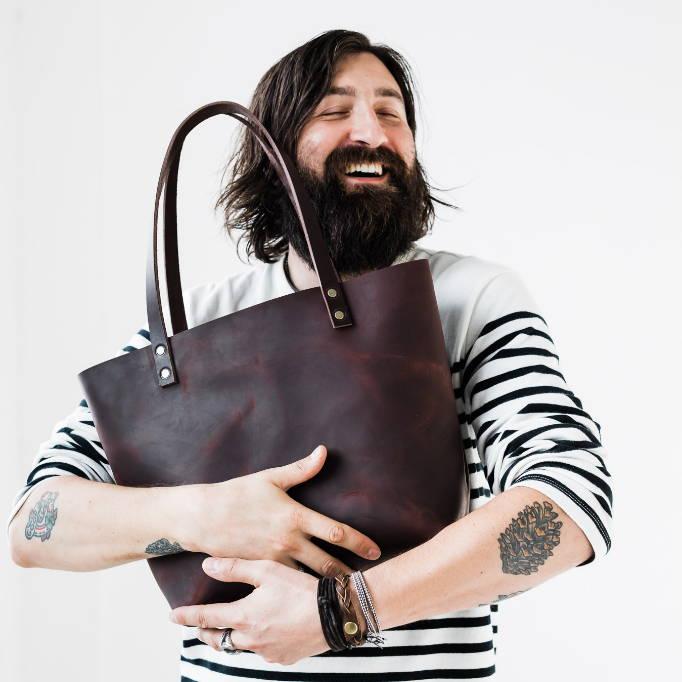 bearded man hugging handmade leather tote bag