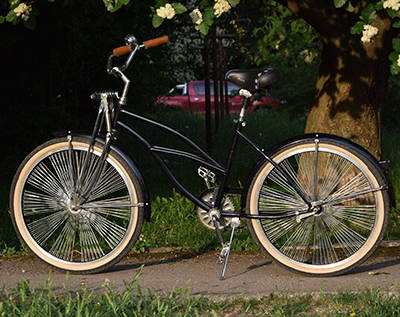An upgraded cruiser bike with new springer forks, wheels, and accessories.