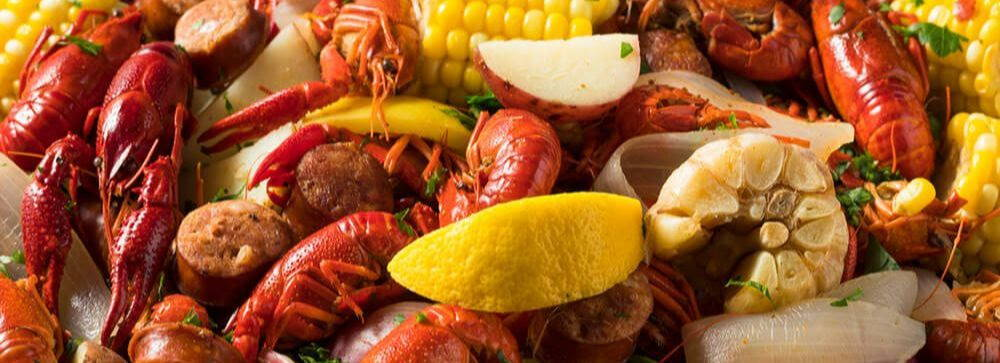 a close up of a crayfish boil with lemon, garlic bulb, corn, potatoes, and onion