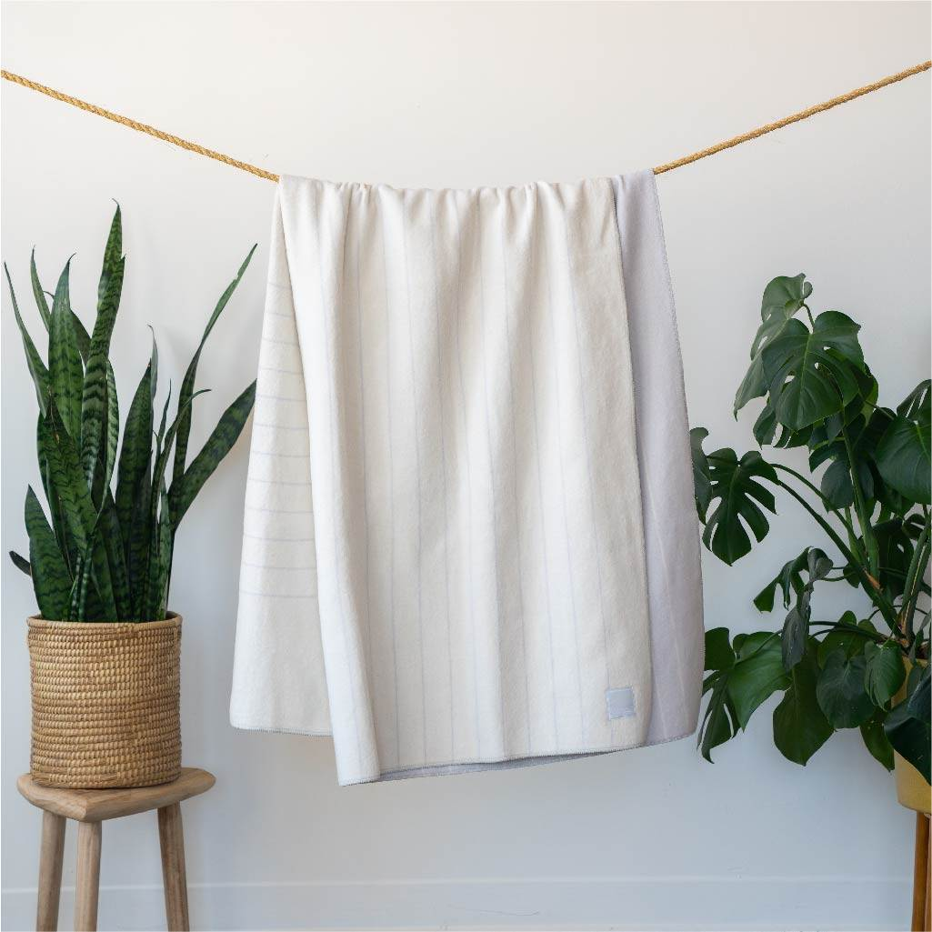 white merino wool blanket hanging on a rope with plants