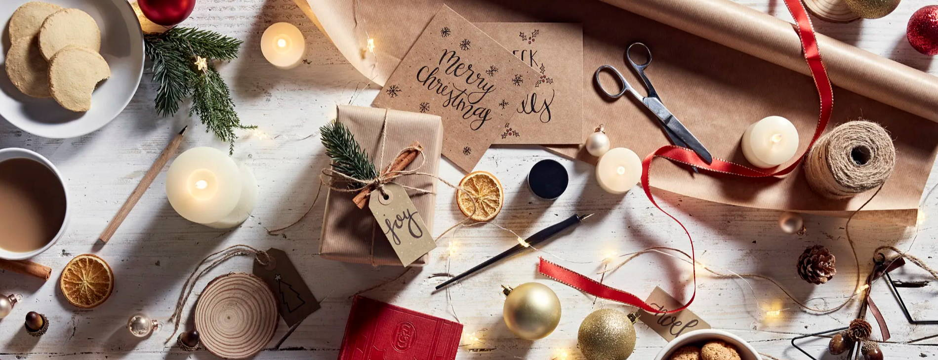 Eingepacktes Geschenk, Verpackungsmaterialien, LED Kerzen, Heißgetränk und Kekse auf einem Tisch