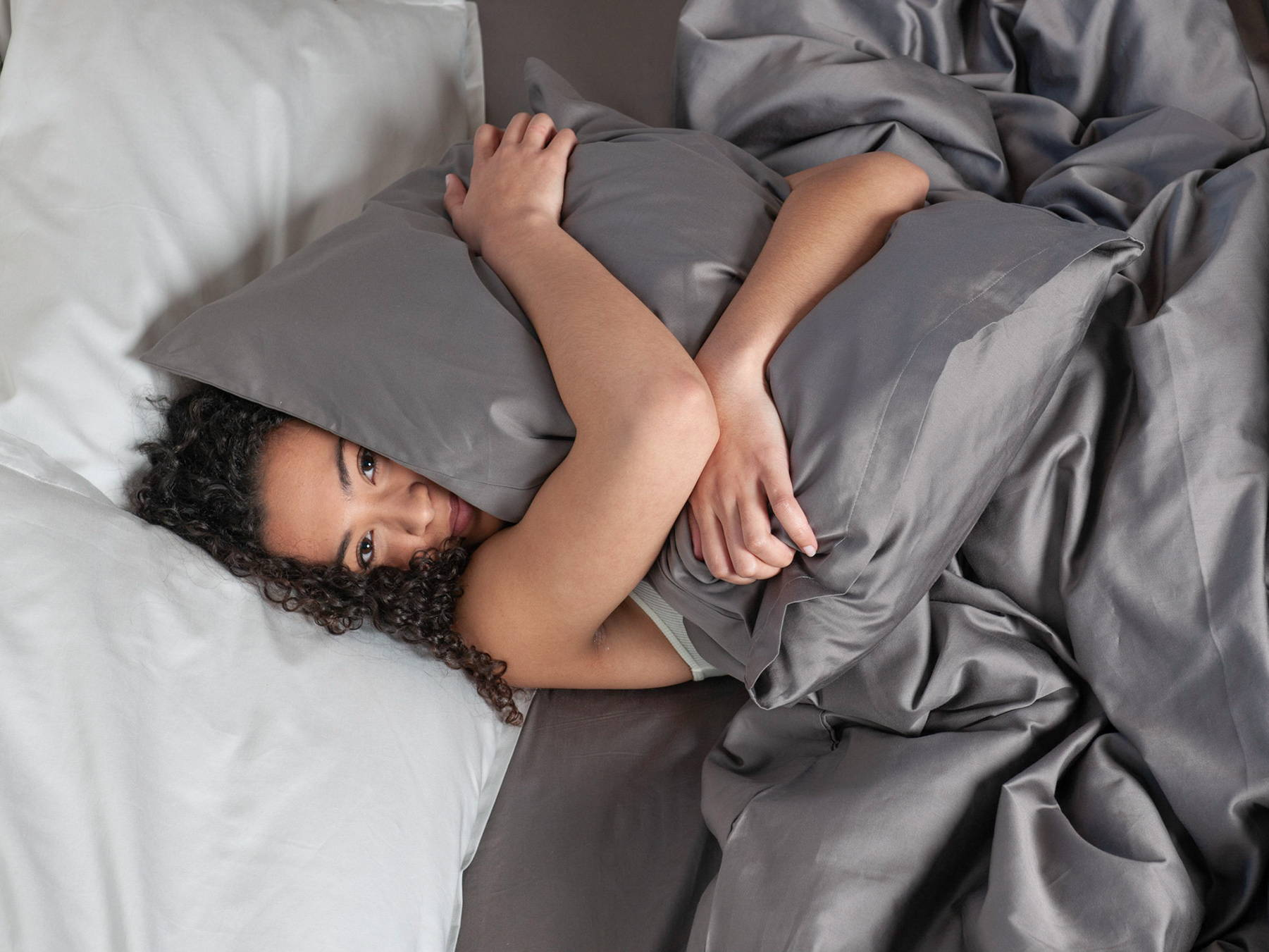 girl wrapped in luxury gray organic cotton bedding