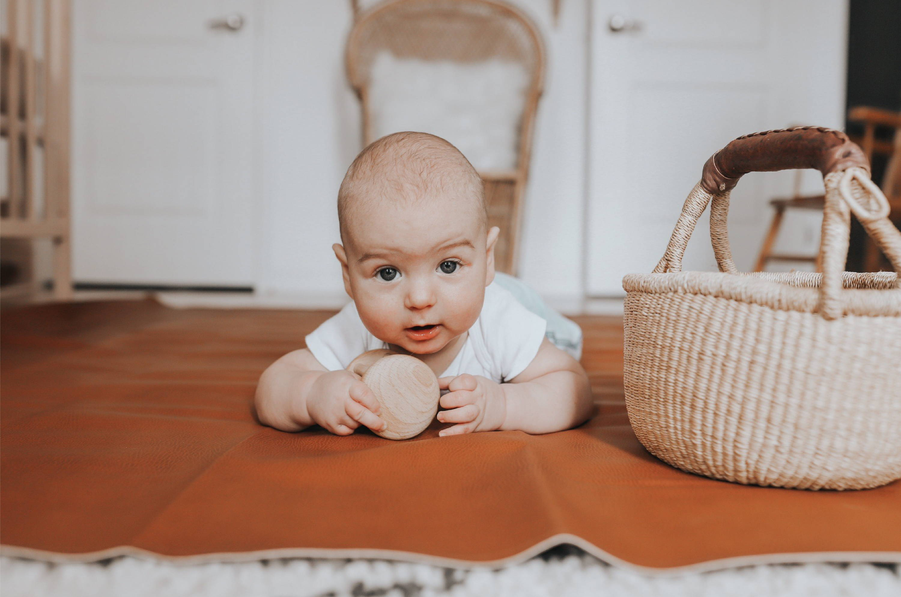 Baby playing on ginger leather mat